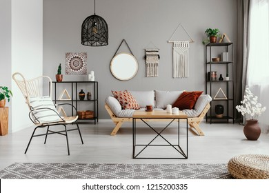 Mirror, macrame and graphic on the grey wall of warm ethno living room with stylish furniture and cozy patterned carpet