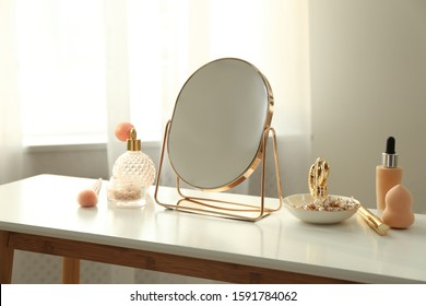 Mirror and makeup products on white table indoors