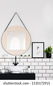 Mirror next to poster and plant in white and black bathroom interior with washbasin. Real photo