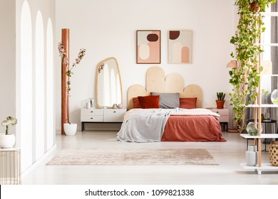 Mirror on cabinet next to orange bed under posters in bright bedroom interior with plants. Real photo