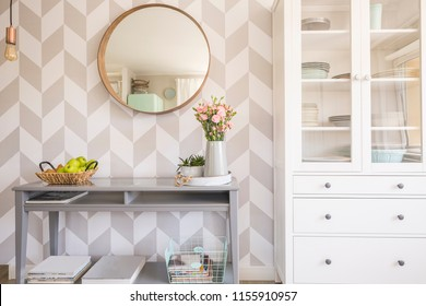 Mirror on patterned wallpaper above grey table with flowers in scandi living room interior. Real photo