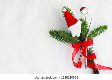mirror and probe, dental instruments with red ribbon for new year on fir, tooth in santa hat on snow. Creative medical christmas stomatology winter background. Health care, hygiene concept. Copy space