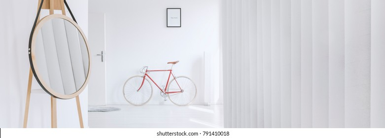 Mirror reflecting grey blinds and a vintage bike standing underneath a poster with transcribed word human