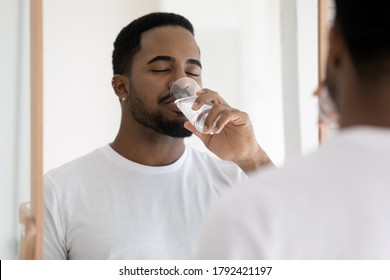 Mirror reflection close up satisfied African American young man wearing white t-shirt drinking pure clean mineral water, standing in bathroom with closed eyes, enjoying morning healthy habit