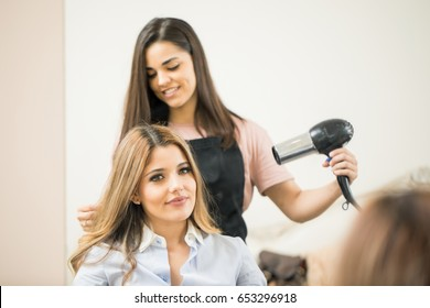 Mirror reflection of a cute hairdresser using a blowdryer on a female customer in a hair salon