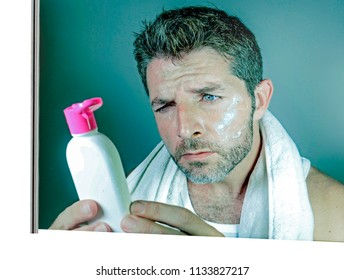 mirror reflection portrait of young confused and attractive man using beauty facial beauty product applying cream and reading the instructions on the lotion bottle in metrosexual male concept