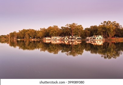 mirror reflection of river houses and trees along Murray river water front near Mildura town on a border between Victoria and NSW at sunrise.