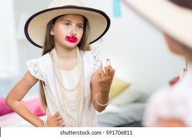 Mirror reflection shot of little girl playing dress up in mothers jewels and hat putting makeup and pink lipstick on, messing it up in smudges and looking displeased with herself