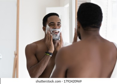 Mirror reflection smiling cheerful African American handsome young man applying shaving foam, standing in bathroom, doing personal hygiene, skincare and morning routine procedure at home