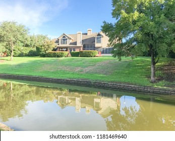Mirror reflection of typical riverside houses surrounded by mature trees in Irving, Texas, USA.
