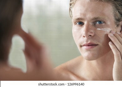Mirror reflection of a young man applying facial cream on face