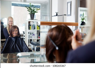Mirror reflection of young woman getting a hairdo by beautician at parlor