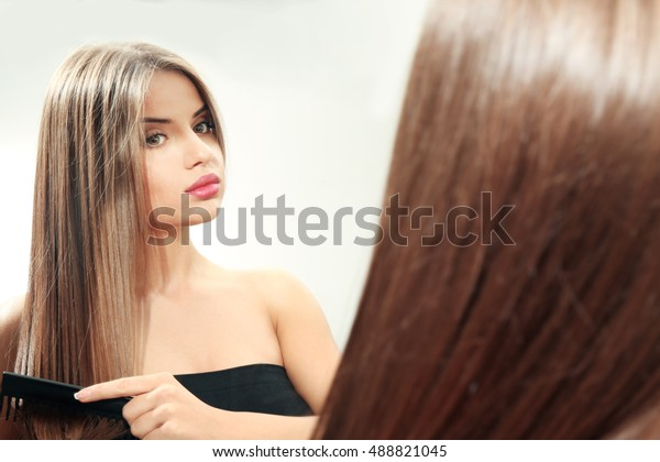 Mirror reflection of young woman making hairdo