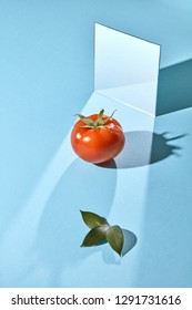 A mirror, a ripe tomato and leaves on a blue background with shadows and a copy of a spacer. Creative food composition