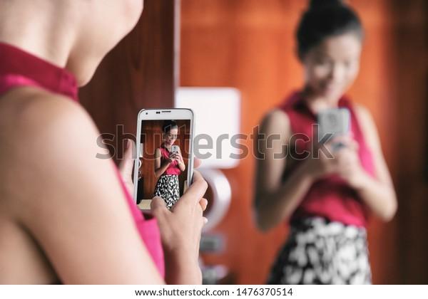 Mujer selfie espejada tomando fotos con el teléfono móvil en el espejo de la tienda de la compra de ropa mirando su traje de moda para la oficina tomando selfies en el vestuario. Pérdida de peso, imagen corporal, autoestima.
