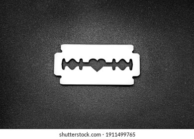 Mirror surface razor blade with a heart-shaped opening in the middle on a black backdrop