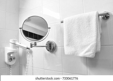 Mirror, terry bath towel and hair dryer hang on the wall in the bathroom. Care facilities