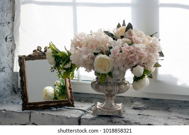 mirror with a vase on the windowsill