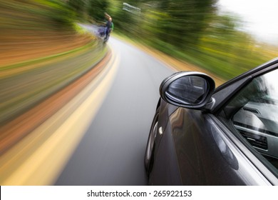 Mirror view of driving car in forest.