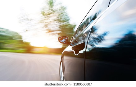 Mirror view of speeding car with blurred road.