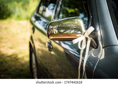Mirror of wedding car decorated with ribbon