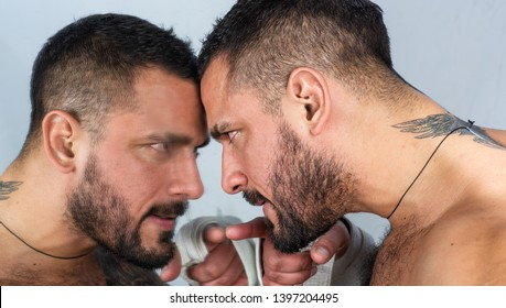 A mirror where a man watching himself. Man and mirror. Bearded hispanic man pointing finger at mirror. Brutal latino man with beard and mustache looking at his reflection in mirror.