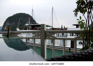 Mirrored reflections of cruise ship and limestone karst formations,  Halong Bay, Vietnam