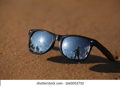 Mirrored safety glasses lie on the sand of a beach against the background of the ocean.