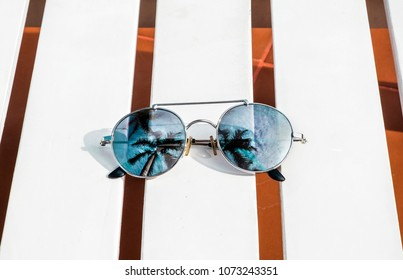 Mirrored sunglasses on white wooden beach chair with palm trees reflection