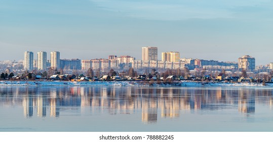 In the mirrored surface of the river Kama, reflects one of the districts of the city of Perm, located on the opposite Bank. Winter.