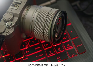 Mirrorless camera and lens against red glow keyboard background