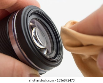 mirrorless system camera lens cleaning. person is cleaning the lens with a cloth