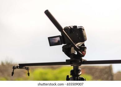 mirrorless video camera on tripod with slider