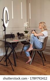 Mirthful Lady mit einem Schlamm in den Händen sitzend auf dem Stuhl am Tisch mit einem Laptop vor ihr. Modernes Ringlicht am Tisch