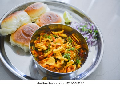 Misal pav is indian breakfast snack item specially famous in Maharashtra region. It is served with spicy gravy containing sprouts with salty snack called farsan. It is eaten with Bread called 'Pav'