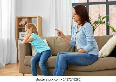 misbehavior, conflict and family concept - angry mother scolding her daughter at home