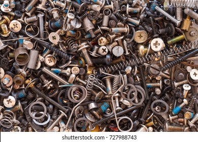 miscellaneous hardware parts including screws washers and springs all jumbled in a pile