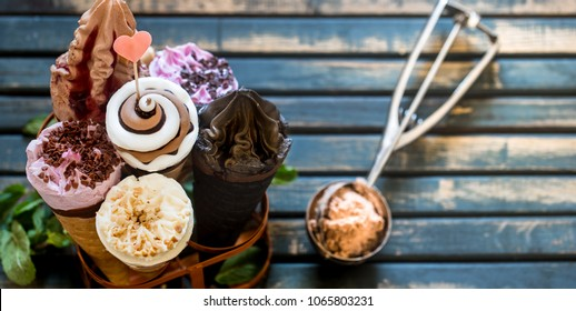 Miscellaneous ice cream cone in a stand on a stylish wooden background, the concept of ice cream and summer