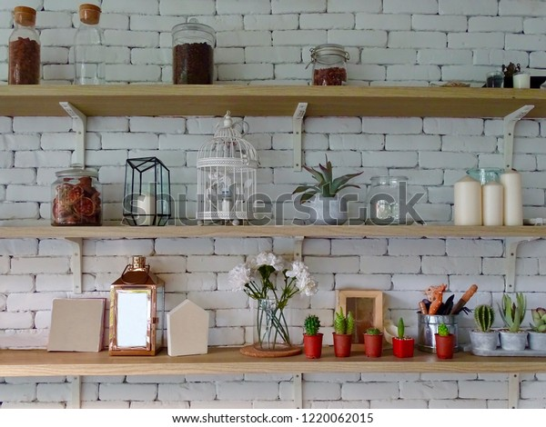 Miscellaneous on the wall shelf. Things on the brick wall shelf. Shelves on a white brick wall. Decorative items on the shelf. Interior design of wall.
