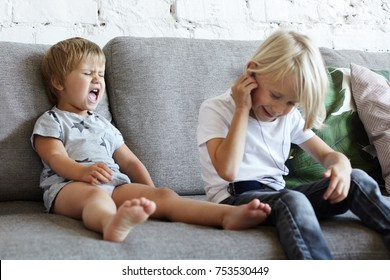 Mischievous blonde schoolboy boy in earplugs sitting on sofa with his unhappy little sister who is crying because he doesn't give MP3 player. Childhood, family, siblings and relationships problems