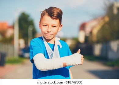 Mischievous boy with broken hand injured after accident showing OK sign