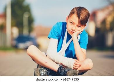 Mischievous boy with broken hand injured after accident during summer sports.