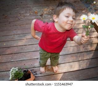 A mischievous boy hands his mother daisies after he has broken her flower pot