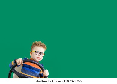 Mischievous boy playing with the steering wheel, on a green background in the studio. Copy space.