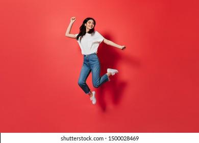 Mischievous girl in white T-shirt and jeans jumping on red background