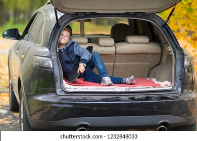 Mischievous little boy with a skateboard sitting in the trunk of a car grinning happily at the camera outdoors in a street in autumn