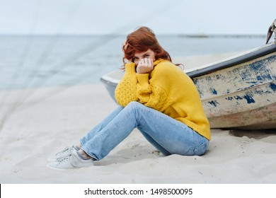 Mischievous tousled young woman peeping at the camera while snuggling into a warm sweater as she relaxes sitting on the sand on a cold autumn beach with wooden dinghy alongside