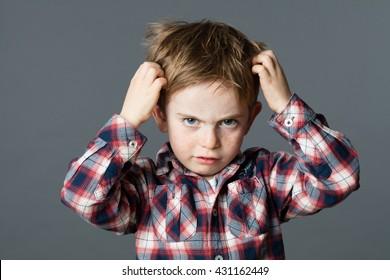 unglückliches 6-jähriges Kind mit Sommersprossen, die sich die Haare für Kopf- oder Allergien kratzen, grauer Hintergrund