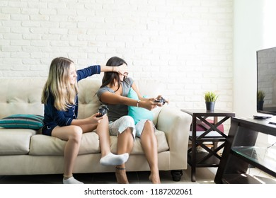 Mischievous young woman covering friend's eyes while playing videogame at home