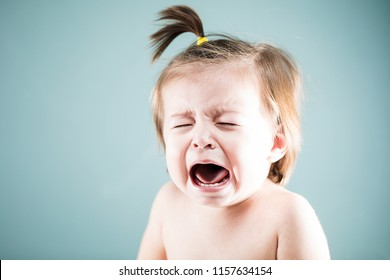 Miserable baby girl crying and looking very upset in a studio